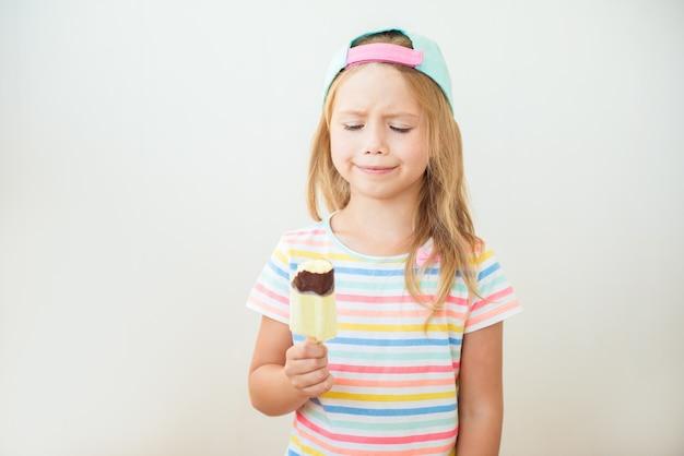 Petite fille mangeant de la glace sucrée sur un bâton