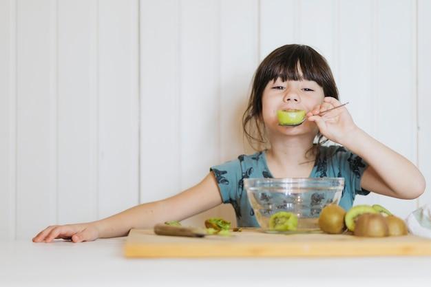 Petite fille mangeant des kiwis