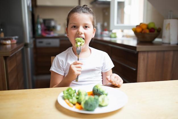 Petite fille mangeant des légumes sains à la maison
