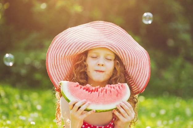 Petite fille mangeant une pastèque rouge.
