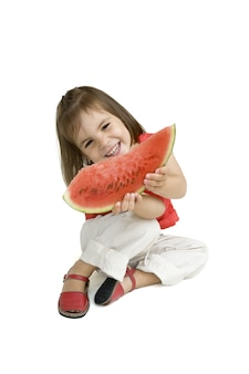 Petite fille mangeant des pastèques isolées