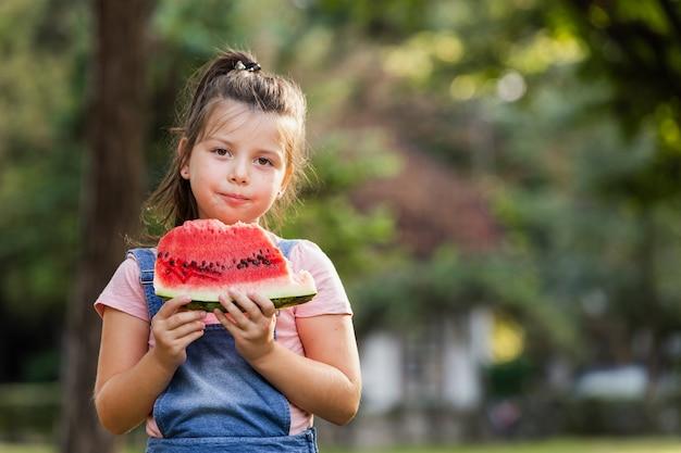 Petite fille mangeant des pastèques en plein air