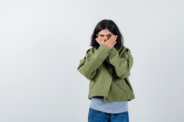 Petite fille en manteau, t-shirt, jeans couvrant la bouche avec les mains et l'air confiant, vue de face.