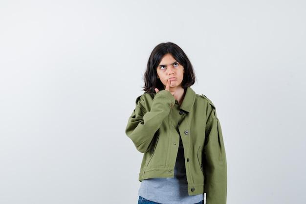 Petite fille en manteau, t-shirt, jeans debout dans une pose de réflexion et l'air réfléchi, vue de face.