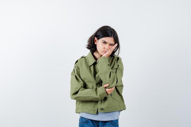 Petite fille en manteau, t-shirt, jeans s'appuyant sur la joue et l'air pensif, vue de face.