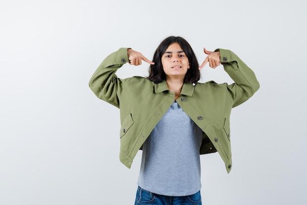 Petite fille en manteau, t-shirt, jeans se pointant et l'air fier, vue de face.