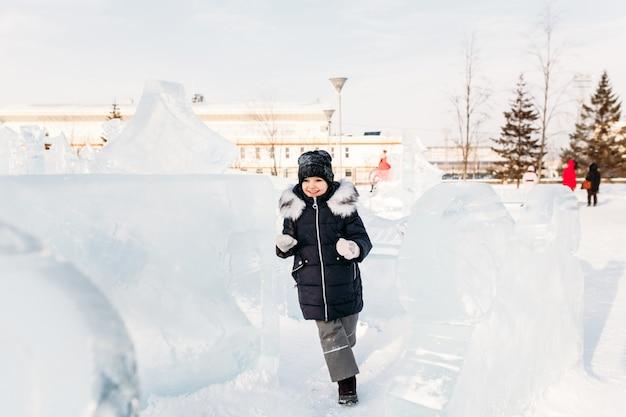 Petite fille marchant en hiver, sculptures de glace d'hiver, chapeau et veste chaude