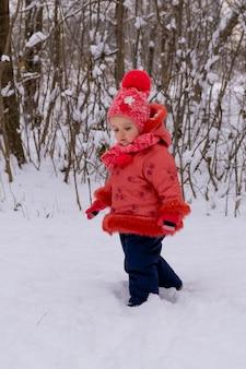 Petite fille marchant sur la neige. l'heure d'hiver.