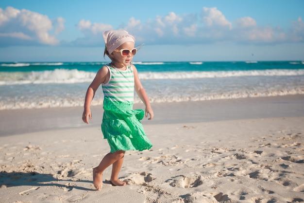 Petite fille marchant sur une plage de sable blanc au mexique
