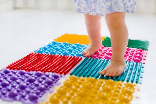 Petite fille marchant sur un tapis de massage
