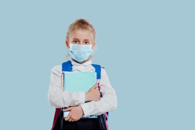 Petite fille avec masque médical et sac à dos a des cahiers et des livres à la main isolés sur fond bleu