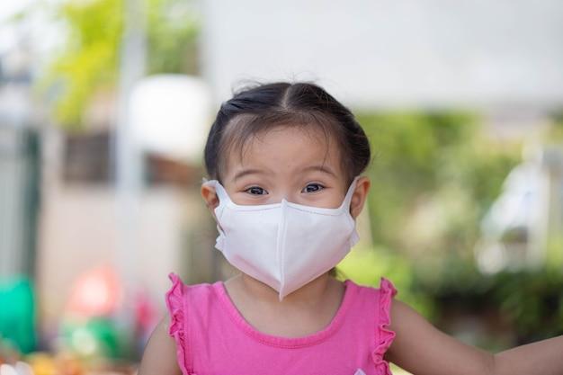 Petite fille avec un masque de santé protège le virus corona.