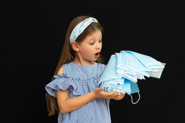Une petite fille avec des masques médicaux sur un fond noir isolé.