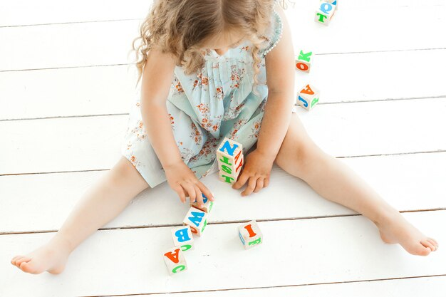 Petite fille méconnaissable jouant avec des cubes abc à l'intérieur
