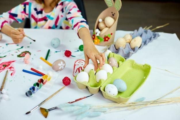 Petite fille méconnaissable prend des oeufs, peinture, dessin avec des oeufs au pinceau à la maison