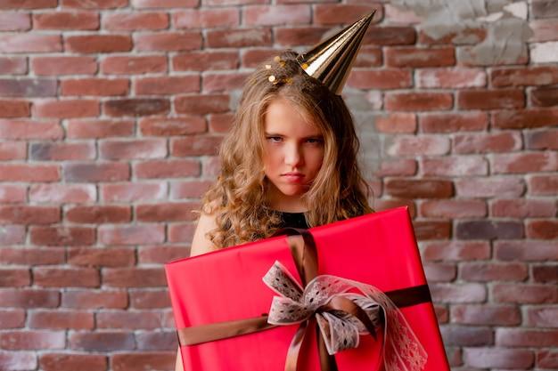 Petite fille mécontente tient un cadeau d'anniversaire