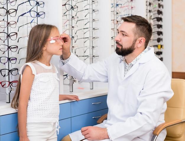 Petite fille et médecin ophtalmologiste choisissent des lunettes