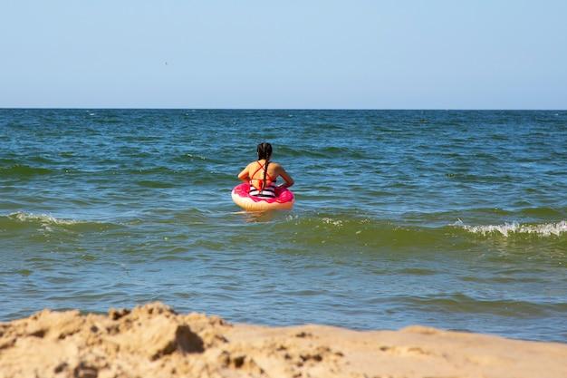 Petite fille sur la mer avec une bouée de sauvetage rose un jour d'été, vacances
