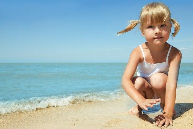 Petite fille sur la mer sous le ciel bleu