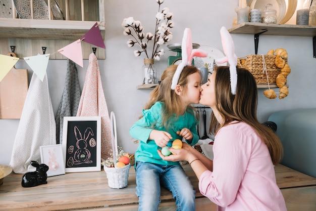 Petite fille et mère dans les oreilles de lapin s'embrasser
