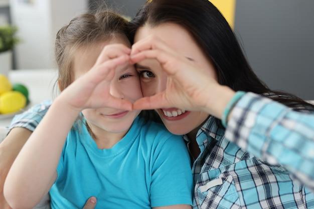 Petite fille et mère étreignant et montrant le coeur avec leurs mains