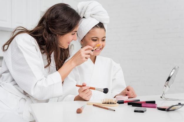 Petite fille et mère faisant leur maquillage ensemble