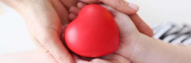 Petite fille et mère mains tenant gros plan coeur jouet rouge