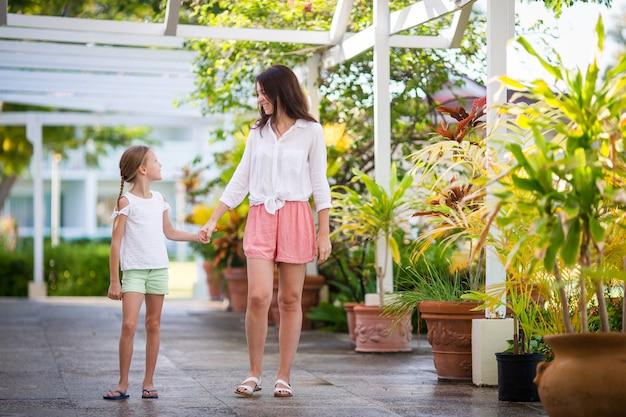 Petite fille et mère marchant dans un hôtel de luxe en vacances d'été