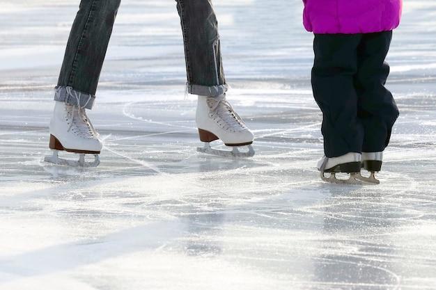 Petite fille avec mère patiner sur la patinoire. sport et divertissement. repos et vacances d'hiver.
