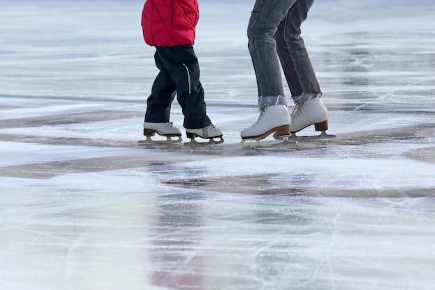Petite fille avec mère patiner sur la patinoire