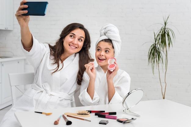 Petite fille et mère prenant un selfie tout en faisant leur maquillage