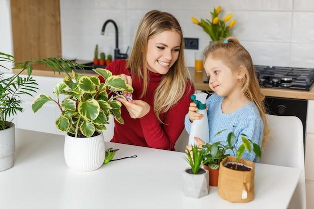Petite fille et mère pulvérisant et nettoyant les plantes d'intérieur. enfant aidant maman à prendre soin des plantes