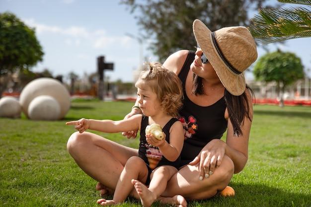 Petite fille et mères en été sur l'herbe parmi les palmiers