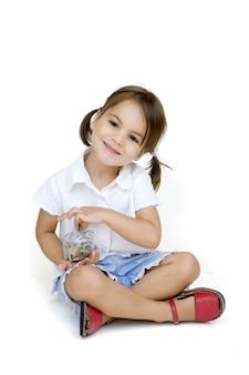 Petite fille met de l'argent dans la tirelire isolée