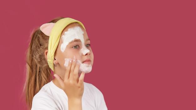Une petite fille met un masque cosmétique sur un rouge isolé