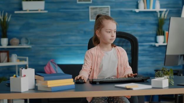 Petite fille mettant le sac à dos sur le canapé et utilisant l'ordinateur