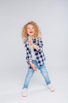 Petite fille avec microphone souriant chantant