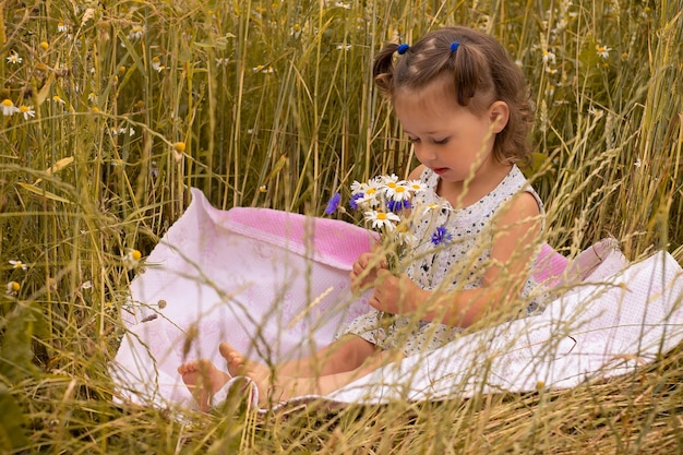 Petite fille mignonne 1-3 dans une robe légère avec un bouquet de bleuets et de marguerites, assise sur un plaid dans un champ d'épillets de seigle en été