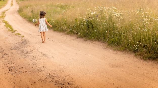 Petite fille mignonne 1-3 dans une robe légère, courant sur un chemin dans le domaine sur un fond d'herbe avec un bouquet de marguerites en été