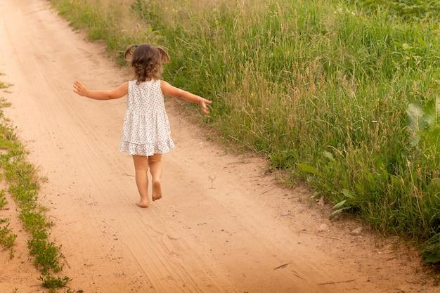 Petite fille mignonne 1-3 dans une robe légère courant sur un chemin dans le domaine sur un fond d'herbe en été