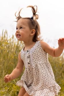 Petite fille mignonne 1-3 dans une robe légère dans le domaine des épillets de seigle en été