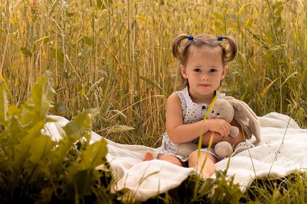 Petite fille mignonne 1-3 dans une robe légère embrasse un lièvre en peluche, assis sur un plaid dans un champ d'épillets de seigle en été.
