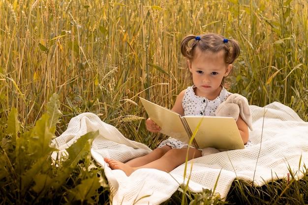 Petite fille mignonne 1-3 dans une robe légère embrasse un lièvre en peluche et lit un livre, assise sur un plaid dans un champ d'épillets de seigle en été.