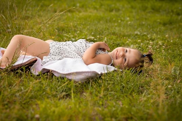 Petite fille mignonne 1-3 dans une robe légère se trouve sur un plaid dans un champ d'épillets de seigle en été