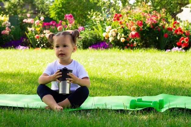 Petite fille mignonne 1-3 dans un t-shirt blanc boit de l'eau après le sport alors qu'elle était assise sur un tapis vert sur l'herbe, sur fond de fleurs