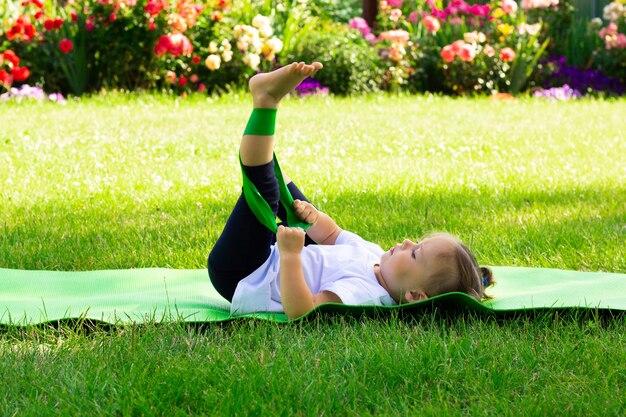 Petite fille mignonne 1-3 dans un t-shirt blanc fait du sport avec un élastique sur un tapis vert sur l'herbe, sur fond de fleurs