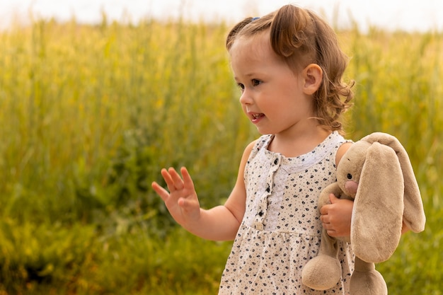 Petite fille mignonne 1-3 avec un lièvre en peluche dans une robe légère agitant sa main dans un champ d'épillets de seigle en été