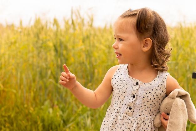 Petite fille mignonne 1-3 avec un lièvre en peluche, dans une robe légère, pointe du doigt quelque chose dans le domaine des épillets de seigle en été.