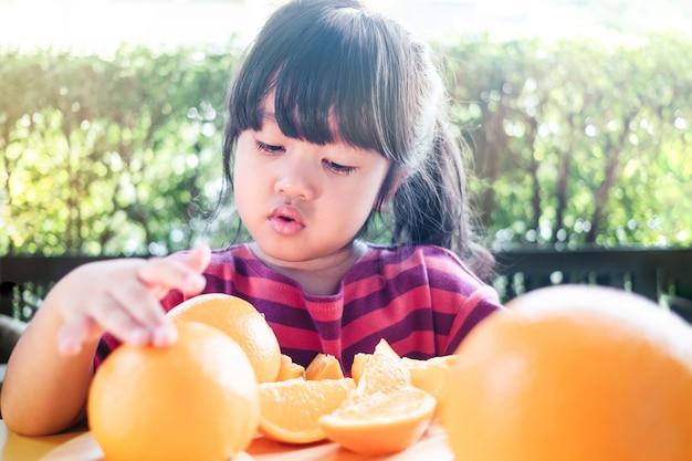 Petite fille mignonne 3-4 ans avec des tranches d'orange sur une plaque de bois.