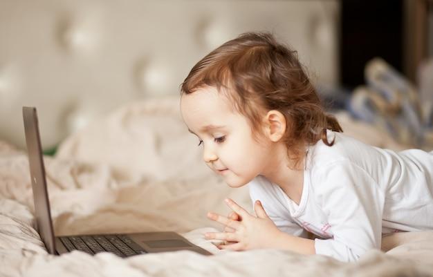 Petite fille mignonne à l'aide d'un ordinateur portable numérique
